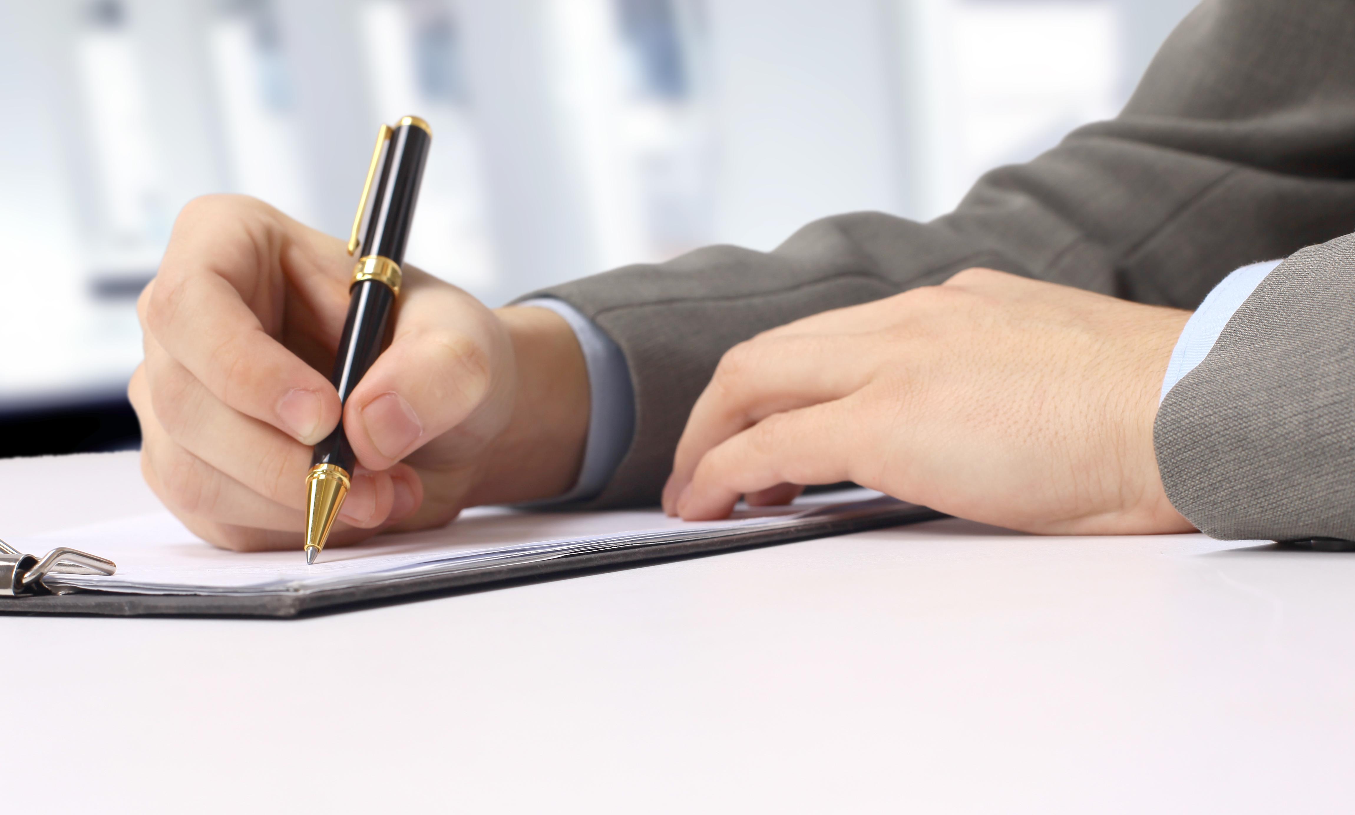 צילום קרוב של יד של גבר אוחז בעט וכותבת על מסמך